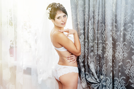 nude bride: Nude bride Striptease. Beautiful girl in white lingerie play with her wedding dress. Young cheerful bride posing in white lingerie