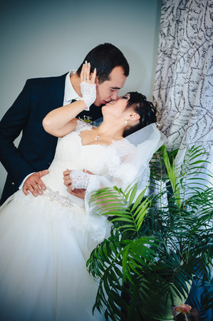 newly married couple: Charming bride and groom on their wedding celebration in a luxurious restaurant. Wedding bouquet of flowers and bridal dress. newly married couple in luxury modern hotel hall