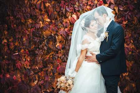 Young couple kissing in wedding gown. Bride holding bouquet of flowers. photo