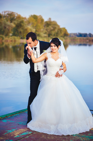 wedding: bride and groom on the seashore. Honeymoon. The bride and groom hugging on the shore of Lake. groom and bride hugging on a green lake. Groom and Bride in a park. wedding dress. Bridal wedding bouquet of flowers photo