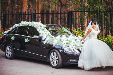 The bride and groom kissing near a black car Standard-Bild