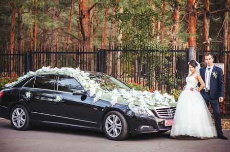 pareja apasionada: La novia y el novio besando cerca de un coche negro Foto de archivo