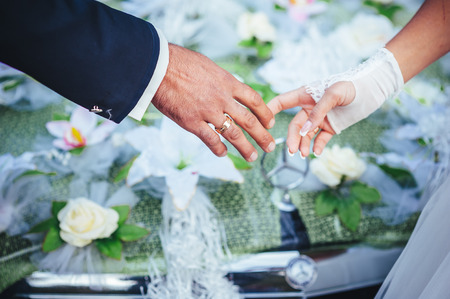 hands of the bride and groom and wedding bouquet on black box car photo