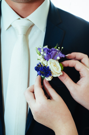 a brides hand putting the boutonniere flower on a groom.