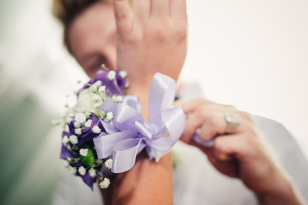 a brides hand putting the boutonniere flower on a groom. photo