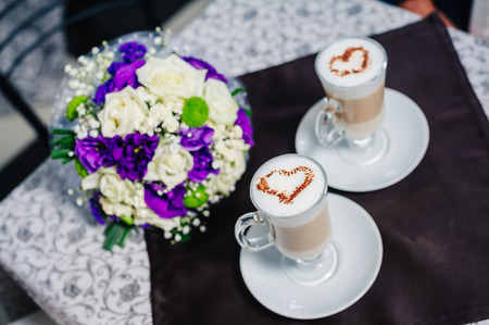 Two cups of coffee with heart on the table, with bridal bouquet photo