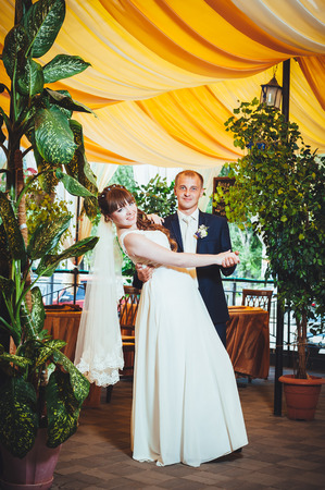 young bride and groom in the park, a wedding bouquet, wedding dresses.