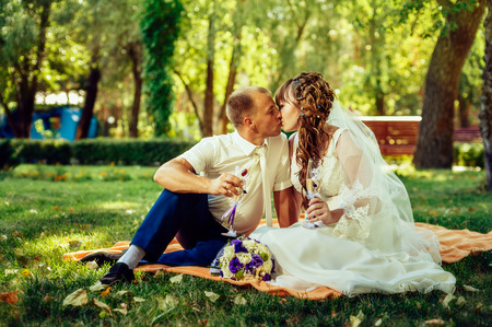 couple just married sitting in park green grass with bouquet of flowers and wine glasses. photo