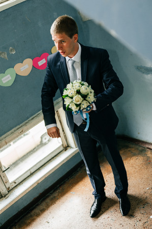Groom holding bouquet. Concept image - young man waiting woman. photo
