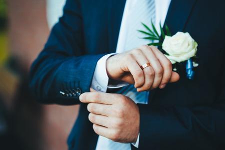 vistiendose: Feliz joven novio el d�a de su boda. Pensamiento novio guapo y poner en su pajarita mientras vestirse para su boda. Hombre cauc�sico hermoso en smoking Foto de archivo