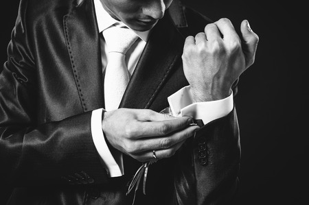 cuffs: Hands of wedding groom getting ready in suit. black studio background. Stock Photo