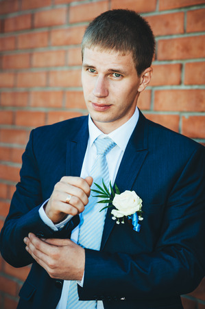 getting dressed: Happy young groom on their wedding day. Handsome groom thinking and putting on his bowtie while getting dressed for his wedding. Handsome caucasian man in tuxedo