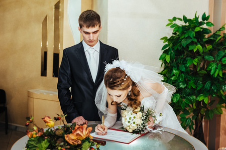 registry: Wedding ceremony. Registry office. A newly-married couple signs the marriage document. Young couple signing wedding documents.