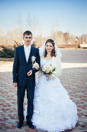 Elegant bride and groom posing together outdoors on a wedding day. photo