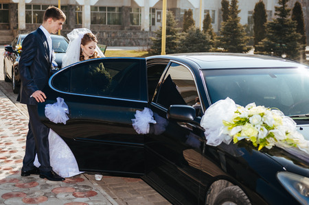 Bride and groom kissing in limousine on wedding-day