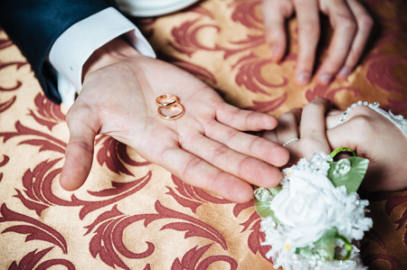 kafe: Couples hands on the table and wedding rings and bridal bouquet flowers Stock Photo