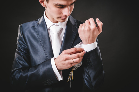 suit  cuff: Hands of wedding groom getting ready in suit. black studio background. Stock Photo