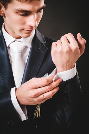 Hands of wedding groom getting ready in suit. black studio background. photo