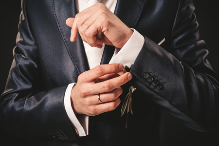cuff links: Hands of wedding groom getting ready in suit. black studio background. Stock Photo