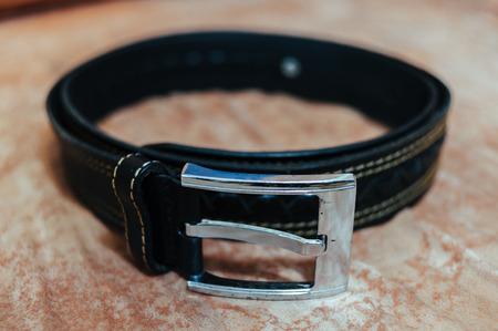 Black leather belt for men on wooden table. men's fashion - accessories dress - leather belt of groom. Standard-Bild
