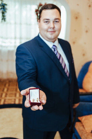 Groom holds a jewelry gift box with gold wedding rings photo