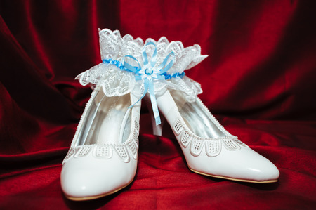 Luxury wedding shoes. Elegant bridal shoes and a white garter on red background photo