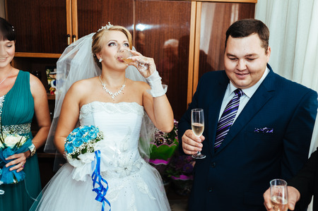 champaigne: bride and groom holding beautifully decorated wedding glasses with champaigne.
