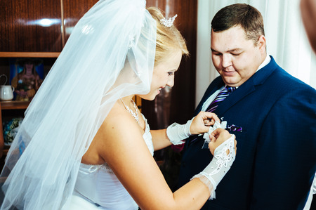 boutonniere: brides hand putting the boutonniere flower on  groom.