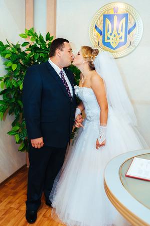 anagrafica: Cerimonia matrimoniale. Ufficio anagrafe. Una coppia appena sposata firma i documenti di matrimonio matrimonio paio document.Young firma.