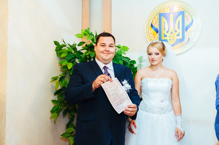 registry: Wedding ceremony. Registry office. A newly-married couple signs the marriage document.Young couple signing wedding documents. Stock Photo