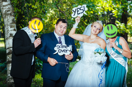 portrait of newlywed couple dancing and having fun with bridesmaids and groomsmen in green sunny park.