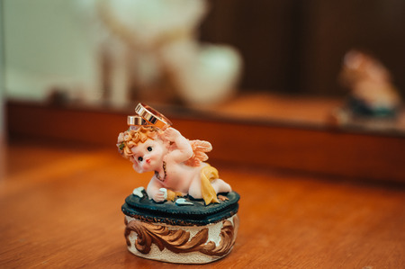 Wedding rings and Cupid statuette, wedding accessories. photo