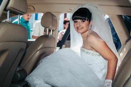 Happy bride sitting in limousine holding flower bouquet.