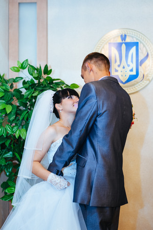 registry: Wedding ceremony. Registry office. A newly-married couple signs the marriage document.Young couple signing wedding documents Stock Photo