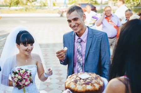 Groom holding slice of traditional wedding round loaf and bride salt it