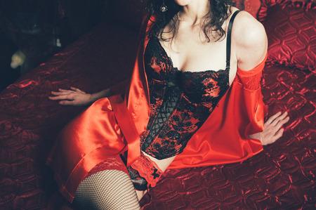 голая женщина: Сексуальная брюнетка стройная женщина позирует в кровать. Леди носить чувственный белье