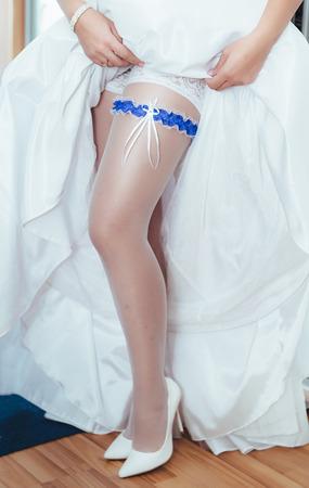 stockings feet: Picture of beautiful female barefoot legs in wedding dress. Bride dresses stockings on feet. Bride putting a wedding garter on her leg