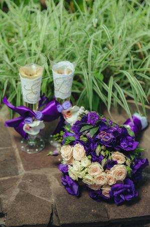 hydrangea macrophylla: wedding bouquet. golden rings and two glasses of shampagne on the background of green grass and stone. Stock Photo