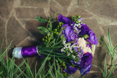 wedding bouquet. golden rings and two glasses of shampagne on the background of green grass and stone. Stock Photo