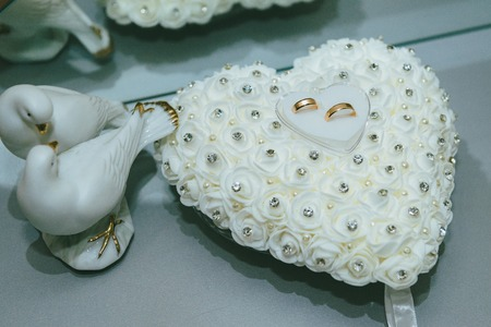Wedding rings on the white heart pillow.