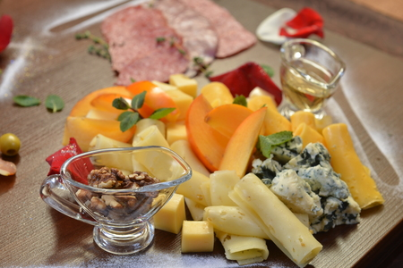 Assorted sliced cheese with mildew, blue, brie, swiss , cheddar, maasdam on the wooden background. fruit and olive oil. Stock Photo