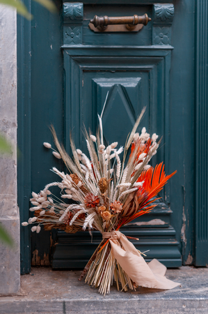 Bunch of fresh flowers with green leaves on the wooden door outside. Beautiful bouquet of tendy flowers decorated for wedding Stock Photo