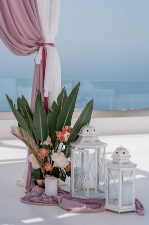 The location of the wedding ceremony on the island of Santorini decorated with bouquets of flowers in glass vases.