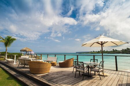 Outdoor restaurant at the beach. Cafe on the beach, ocean and sky. Table setting at tropical beach restaurant. Dominican Republic, Seychelles, Caribbean, Bahamas. Relaxing on remote Paradise beach. Stock Photo