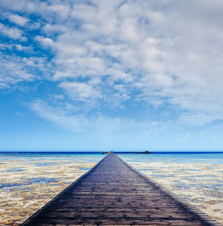 Beautiful view of the tropical coast with a long . A large wooden pier is on the sandy beach of the resort. Landscape of the sea coast.
