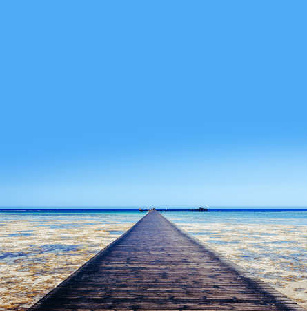 A large wooden pier is on the sandy beach of the resort. Landscape of the sea coast. Standard-Bild