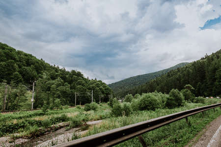 Panoramic view of river and mountain while a train is passing by. Standard-Bild