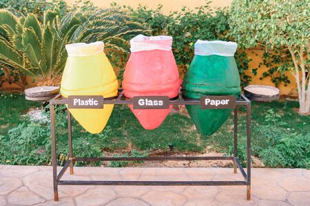 three bins for recycling. sorting debris - plastic, glass and paper. Closeup photo of colorful pots used as garbage containers. It is very important for our planet and ecology to sort your wastes. Stockfoto - 150266733