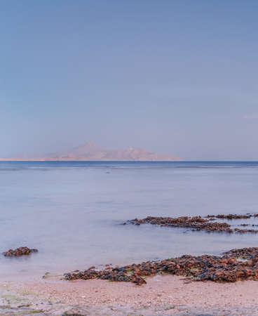 Soft sea ocean waves wash over golden sand background. Sunset, sunrise, sun. Standard-Bild
