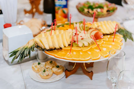 Dish with pineapple and orange slicing. Fruit plate with beautifully cut oranges and pineapple.